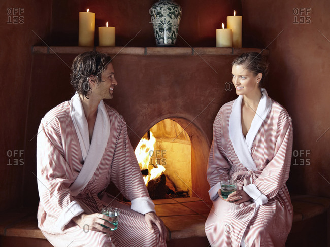 Caucasian couple in robes sitting by fire