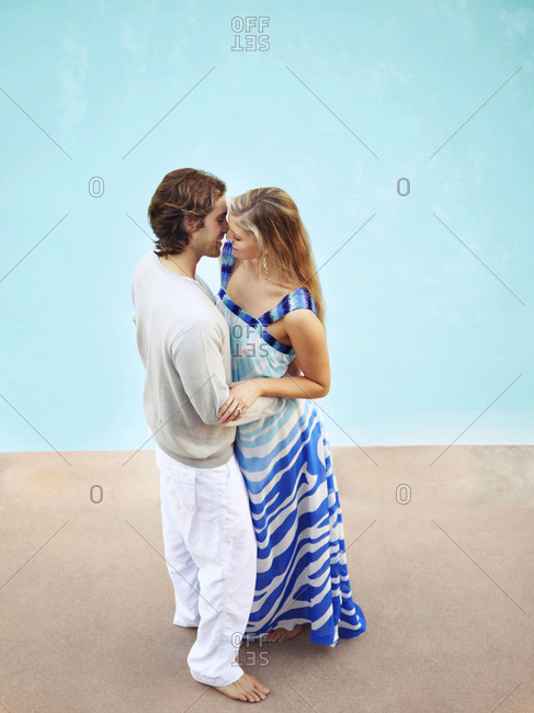 Caucasian couple kissing at poolside
