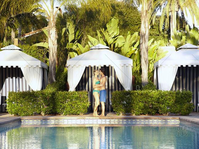 Caucasian couple hugging at poolside