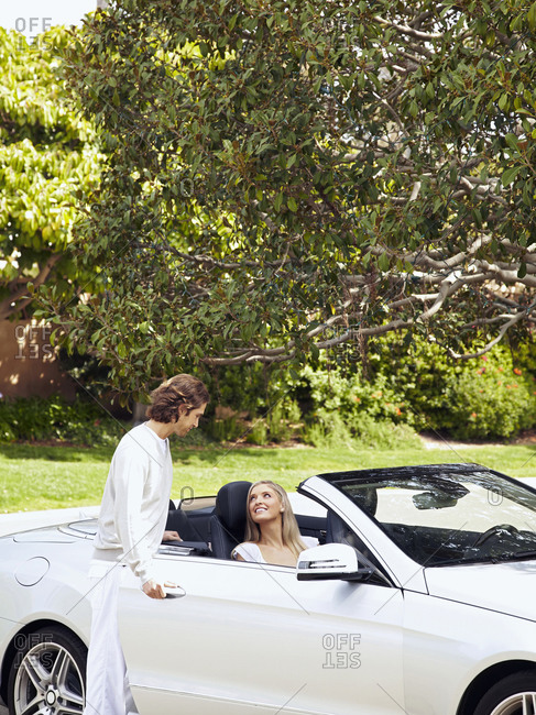 Caucasian man helping wife into convertible