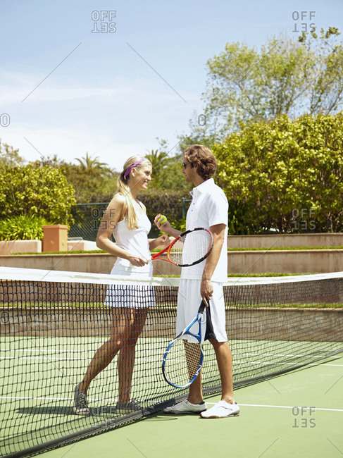 Caucasian couple playing tennis together