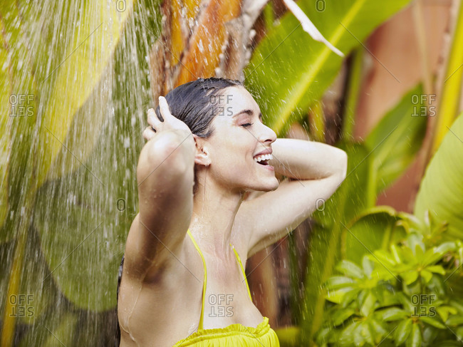 Caucasian woman in bikini showering outdoors