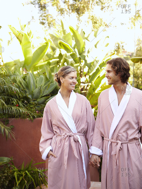 Caucasian couple in robes holding hands