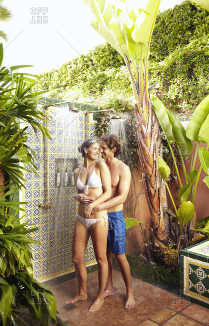 Caucasian couple taking shower together outdoors
