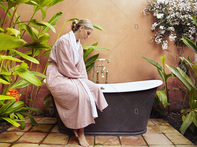 Caucasian woman in robe filling old-fashioned tub