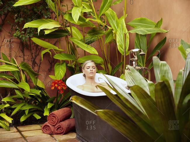 Caucasian woman soaking in old-fashioned tub