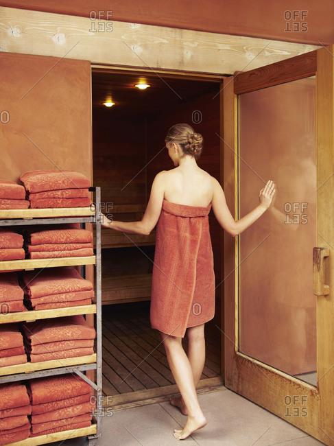 Caucasian woman entering hot sauna