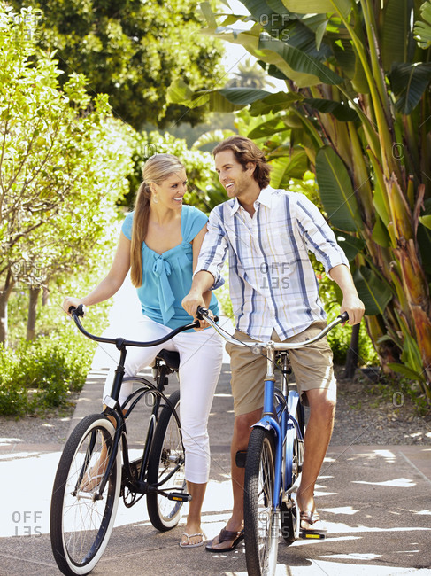 Caucasian couple riding bikes together