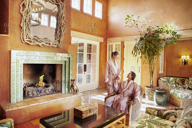 Caucasian couple in robes in resort lounge area