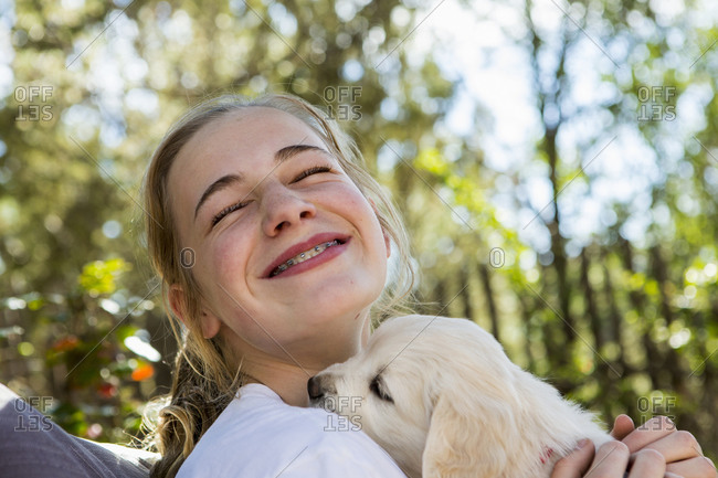 Teenage girl holding a English golden retriever puppy