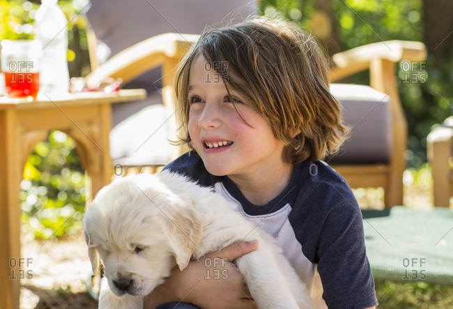 6 year old boy holding an English golden retriever puppy