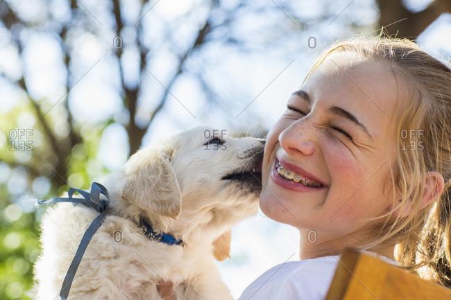 An English golden retriever puppy licking the cheek of a teenage girl.