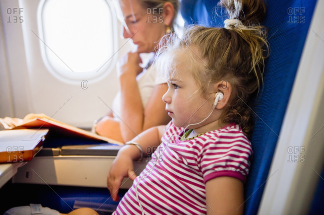 young girl wearing headphones on airplane