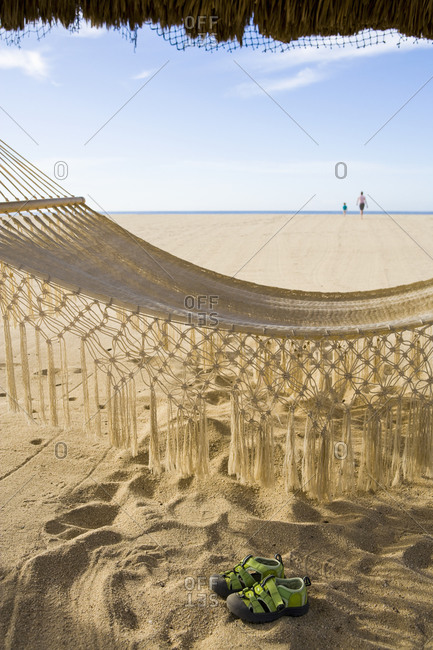 A hammock slung under a beach cabana, footprints and a pair of trainers on the white sand