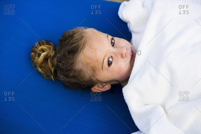 Portrait of 3 year old girl wrapped in white towel