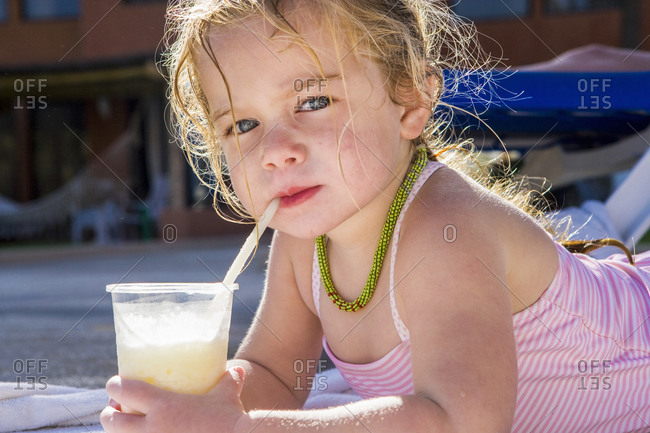 Portrait of 3 year old girl sipping a drink