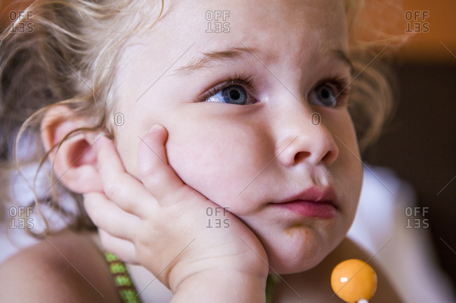 Portrait of 3 year old girl with a lollipop