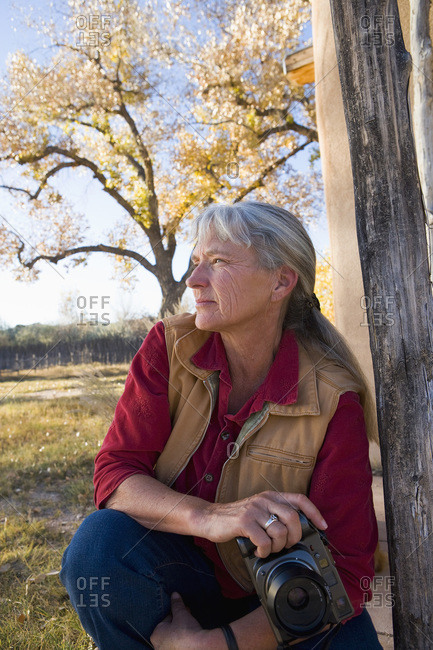 Mature woman at home on her property in a rural setting, holding a camera