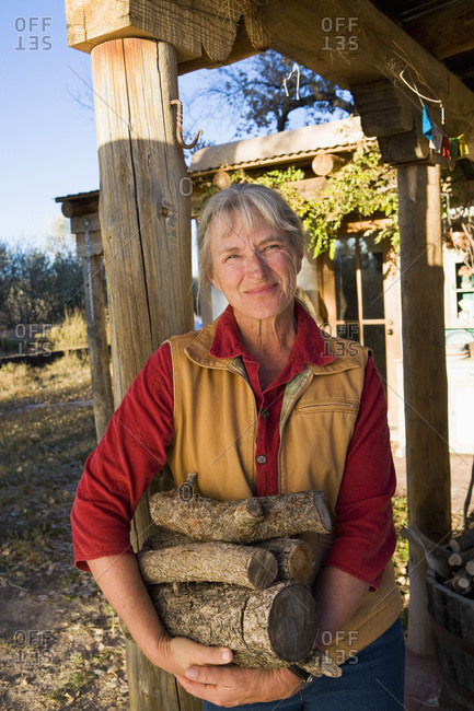 Mature woman at home on her property in a rural setting carrying logs