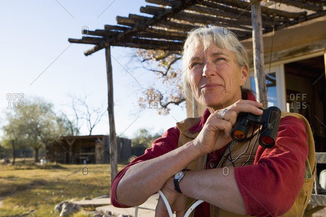 Mature woman at home on her property in a rural setting holding binoculars