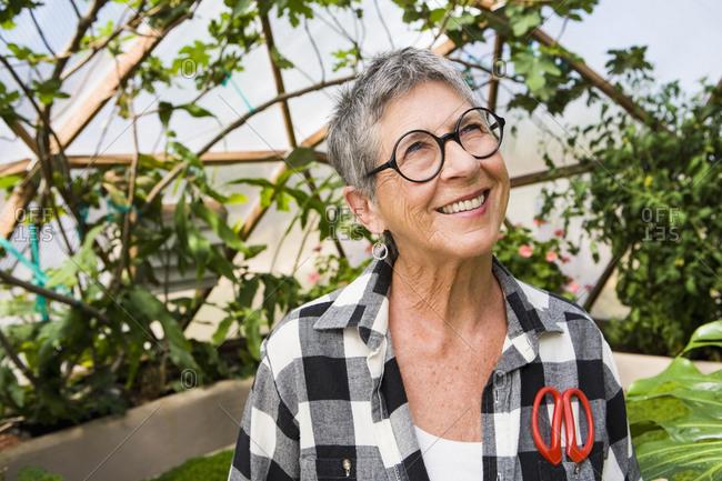 Senior woman gardening in geodesic dome