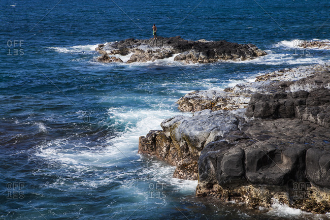 Black laval rocks on a jagged coastline with waves breaking, one person standing on an outcrop.