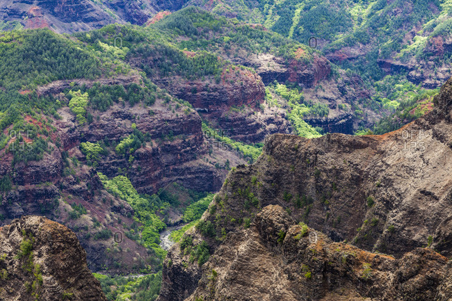 Elevated view of deep canyons, green fertile valleys and steep peaks of an island landscape