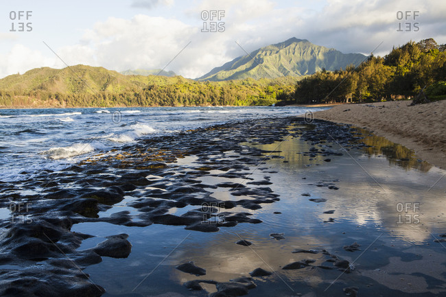 Low tide at a beach, rock formations in the sand and view of mountains and thick forest