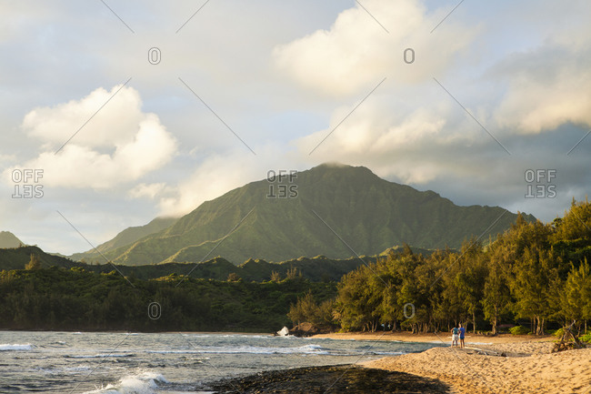 Sunset on a sandy beach with woods and view to a mountain peak.