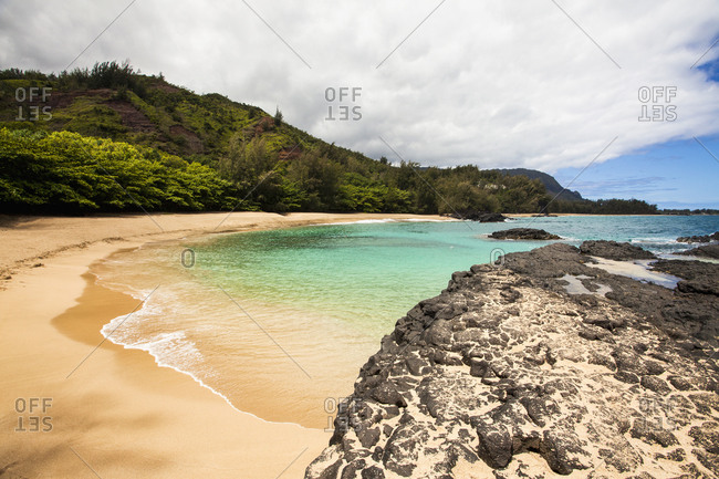 Laval rocks and headland on a Hawaiian coastline and a sweeping sandy beach.