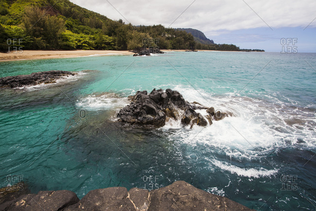 A bay and headland with rocky shore, sand and turquoise water.