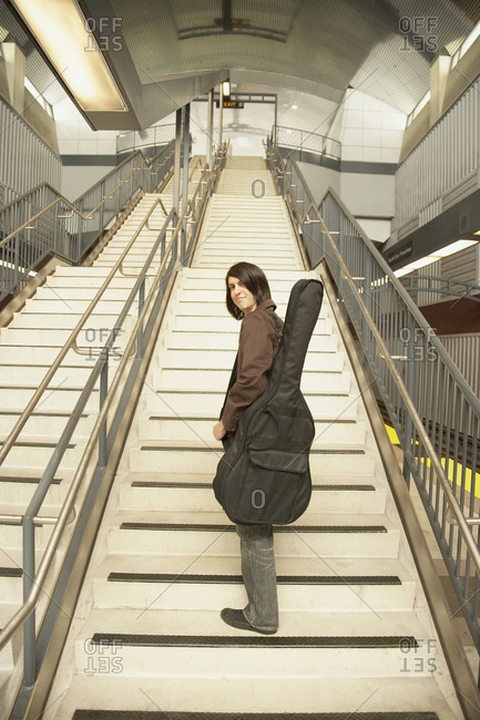 Man with guitar walking up stairs