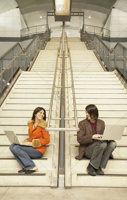 Man and woman sitting on stairs using laptops