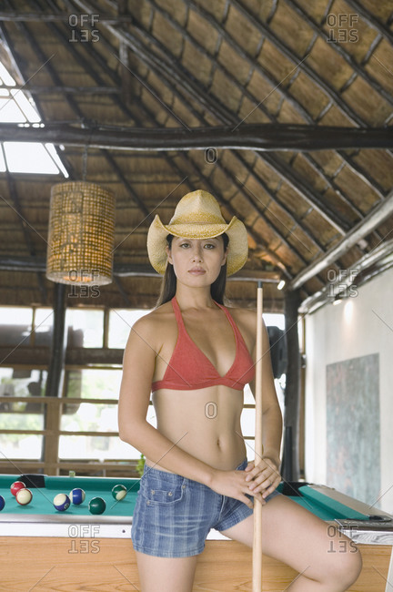 Portrait of woman wearing cowboy hat playing pool