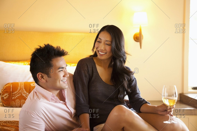 Asian couple drinking wine on bed