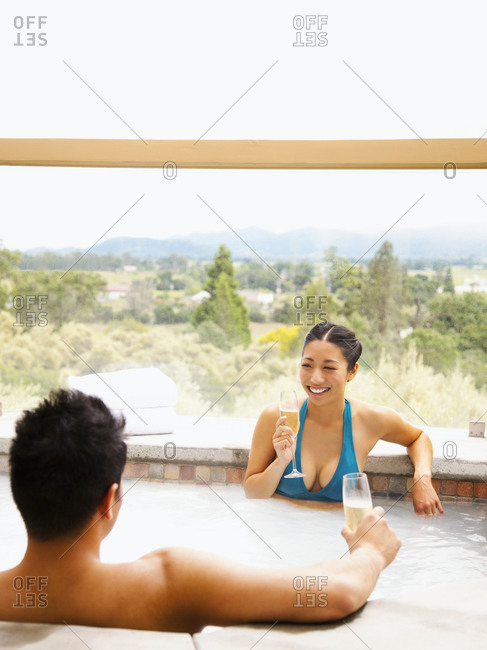 Asian couple drinking champagne in hot tub
