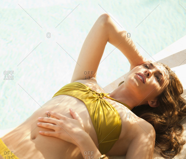 Caucasian woman in bikini laying near swimming pool