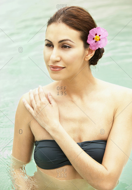 Close up of woman standing in swimming pool with pink flower in her hair looking out