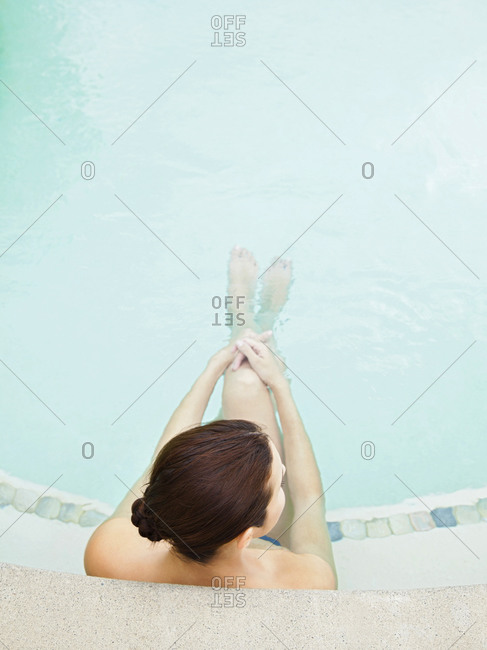 Overhead view of a woman sitting in pool with legs outstretched at a luxury resort