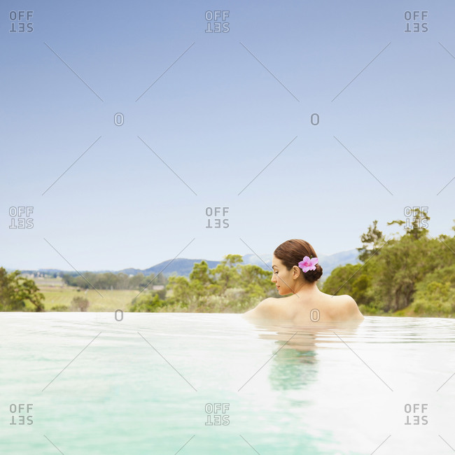 Woman resting in an infinity pool at a luxury resort overlooking Napa Valley, California