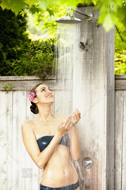 Woman in bikini taking an outdoor shower at a luxury spa