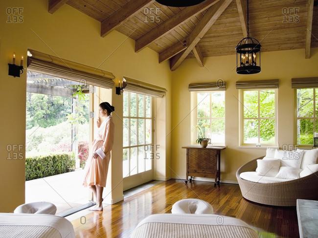 Woman in bathrobe standing in doorway of massage room at a luxury spa
