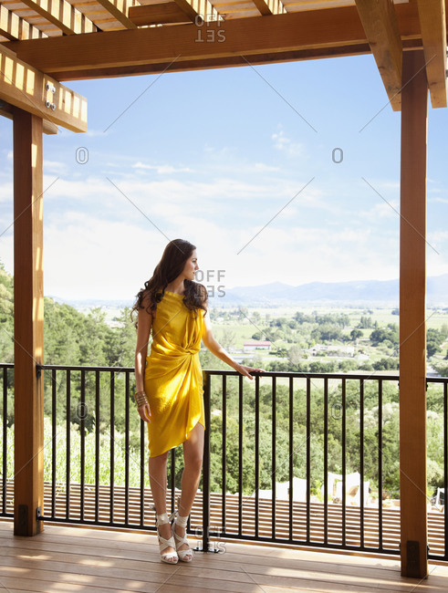 Woman in yellow dress looking out over Napa Valley view from deck of luxury resort