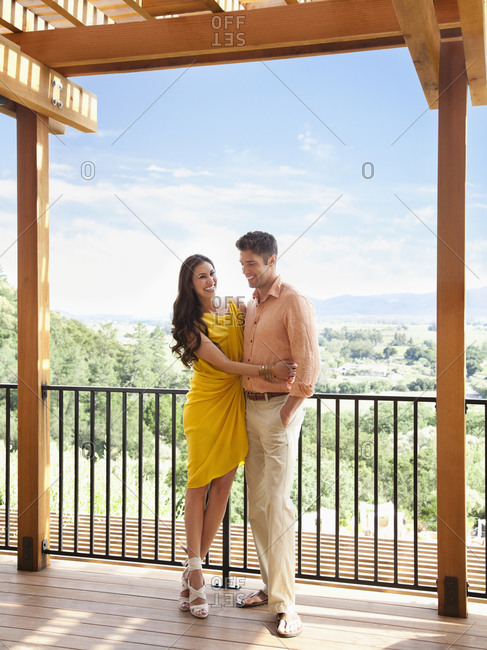 Young couple hugging on deck of luxury resort overlooking view of Napa Valley wine country