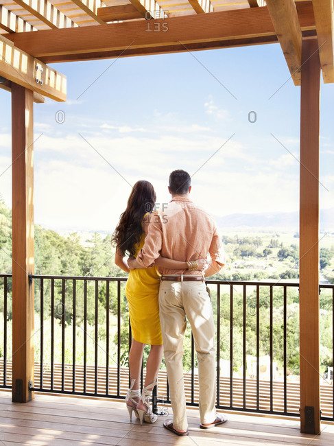 Young couple looking at view of  Napa Valley wine country from deck of luxury resort