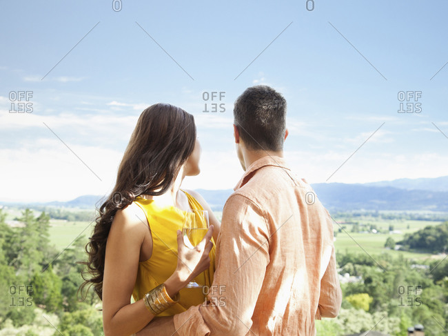 Close up of couple relaxing with a glass of wine at a luxury resort overlooking view of Napa Valley