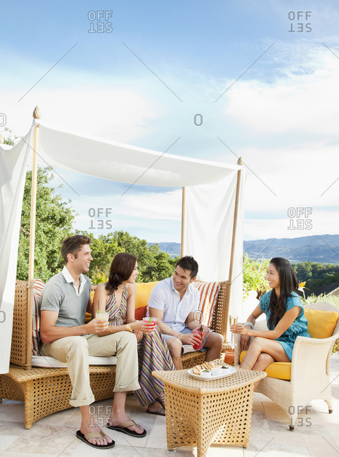 Multi ethnic couples in outdoor lounge by the pool at a luxury resort and spa in Napa Valley, California