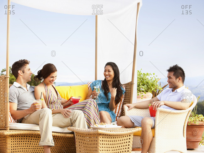 Multi ethnic group drinking in outdoor lounge at a luxury resort and spa in Napa Valley, California