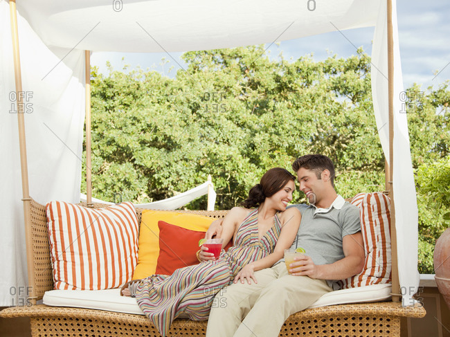 Couple drinking in outdoor lounge by the pool at a luxury resort and spa in Napa Valley, California