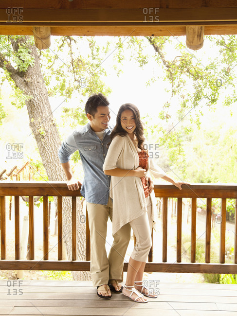 Chinese couple leaning on deck railing at a luxury spa and resort in wine country California